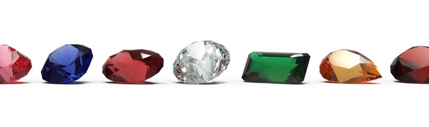 Different colors and cuts of gemstones in a row on a white background.