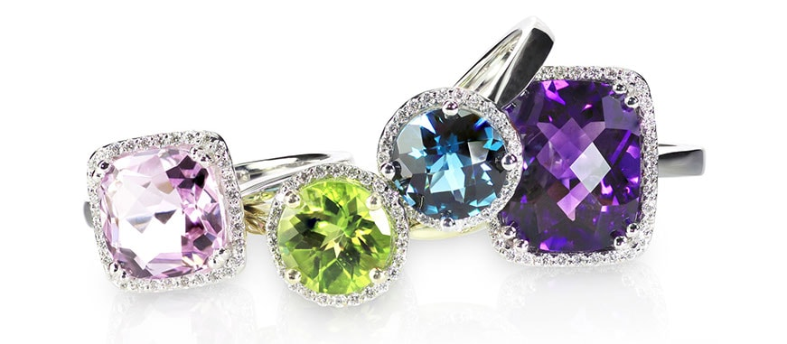 Pink, green, blue, and purple gemstone rings on a white background.