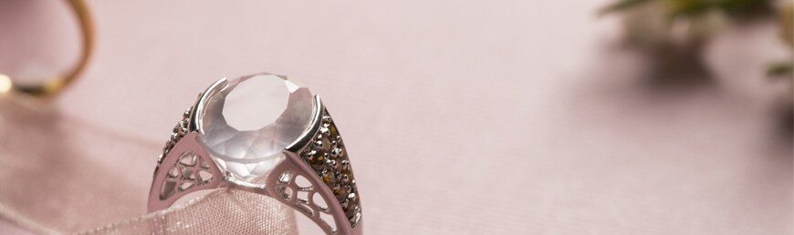 Close up of pink gemstone silver ring on a pink background.