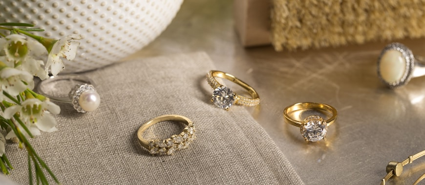 A pearl ring and three diamond rings resting on a cloth. A bristle brush and white bowl and white flowers are in the background.