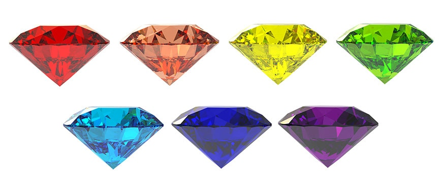 Different colors of gemstones in a row on a white background.