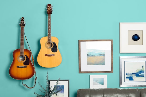 Acoustic guitars hanging on wall with other art in living room.