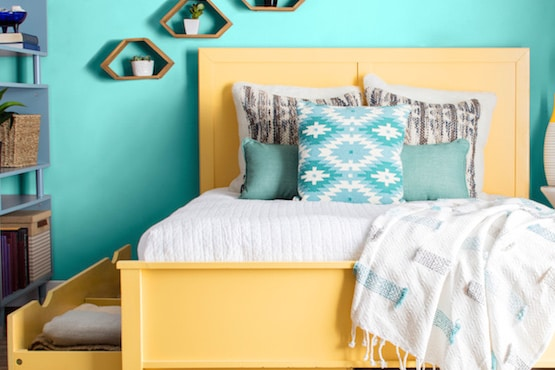 Bedroom with a yellow bedframe and bright aqua walls.